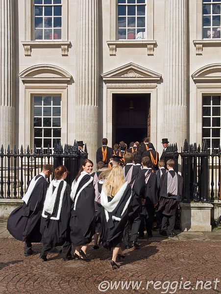 Smiling Queens' College Graduands entering the Senate House to graduate, King's Parade, Cambridge, England